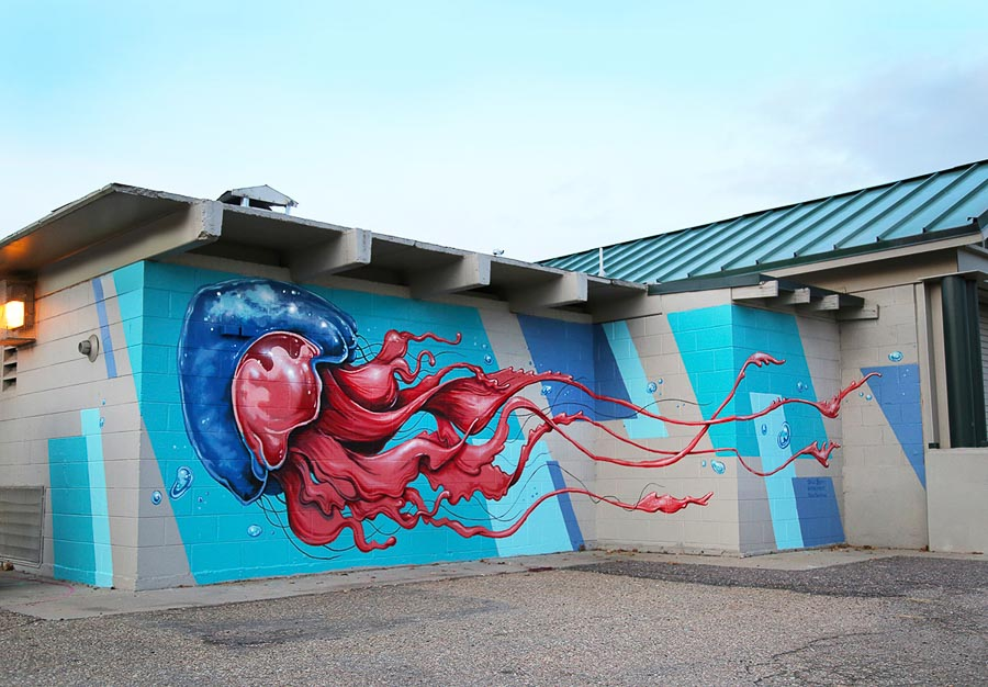 I was hired by Denver Arts & Venues to create a piece on the Ruby Hill Public pool house. The pool house had often been vandalized before the mural and they wanted to brighten up the area. I painted the building with a large jellyfish on one side and a large octopus wrapping around the building on the other side. I used blue graphic shapes to give the piece some movement and a more modern feel. —Patrick Maxcy